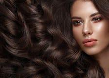 Schönes Brunettemodell: Locken, klassisches Make-up und volle Lippen Das Schönheitsgesicht lizenzfreies stockbild