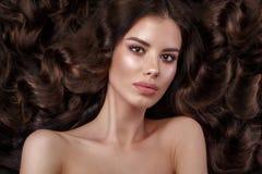 Schönes Brunettemodell: Locken, klassisches Make-up und volle Lippen Das Schönheitsgesicht stockbilder