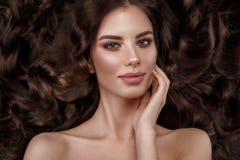 Schönes Brunettemodell: Locken, klassisches Make-up und volle Lippen Das Schönheitsgesicht lizenzfreie stockbilder