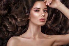 Schönes Brunettemodell: Locken, klassisches Make-up und volle Lippen Das Schönheitsgesicht stockbild