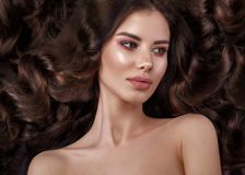 Schönes Brunettemodell: Locken, klassisches Make-up und volle Lippen Das Schönheitsgesicht stockfotografie
