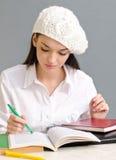 Schönes Studentenmädchen, das ein Barett trägt. Stockbild