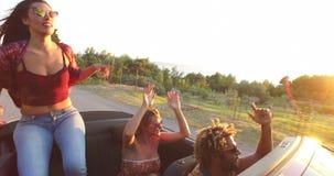 Schönes Brunettetanzen beim Sitzen auf Haube des Kabrioletts stock footage