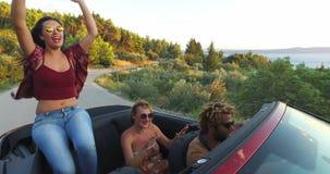 Schönes Brunettetanzen beim Sitzen auf Haube des Kabrioletts stock video footage