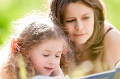 Schönes Buch des kleinen Mädchens Lesemit Ger-Mutter Lizenzfreies Stockfoto