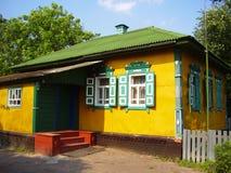 Schönes buntes ukrainisches Dorfhaus außen mit rotem Portal und Grün, weiße Fenster mit Fensterläden Stockfoto