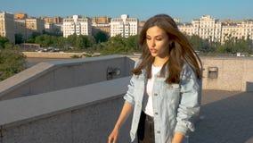 Schönes chanetka mit dem langen Haar singt in der Stadt auf einem Sonnenunterganghintergrund stock video footage