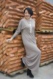 Schönes chinesisches Mädchen, das nahe bei den neuen Ziegelsteinen steht lizenzfreie stockbilder