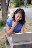 Schönes chinesisches Mädchen misstrauisch über Laptop stockbild