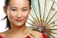 Schönes chinesisches Mädchen mit traditionellem selbst gemachtem Regenschirm Stockbild