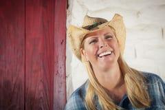 Schönes Cowgirl gegen alte Wand und rote Tür Lizenzfreie Stockfotografie