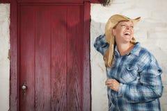 Schönes Cowgirl gegen alte Wand und rote Tür Stockbild