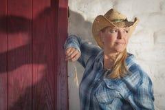 Schönes Cowgirl gegen alte Wand und rote Tür Lizenzfreies Stockfoto