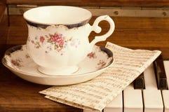 Schönes Cup auf dem Klavier Stockbilder