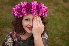 Schönes curvy Mädchen mit einer Blumenkrone, die ihr Auge bedeckt lizenzfreie stockfotos
