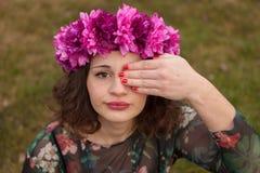Schönes curvy Mädchen mit einer Blumenkrone, die ihr Auge bedeckt stockbilder