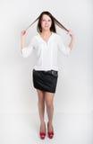 Schönes dünnes Mädchen in einem kurzen schwarzen Rock, in einer weißen Bluse und in roten Schuhen mit den hohen Absätzen, sein Ha Lizenzfreie Stockfotos