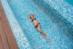 Schönes dünnes sexy blondes Mädchen in einem schwarzen Badeanzug legt in das Pool Lizenzfreie Stockfotos