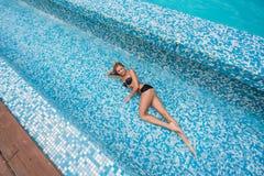 Schönes dünnes sexy blondes Mädchen in einem schwarzen Badeanzug legt in das Pool Stockbilder