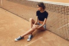 Schönes dünnes Tennismädchen mit dem dunklen Haar trägt die Sportkleidung und wirft auf Tennisplatz auf Stockbild