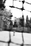 Schönes dünnes Tennismädchen mit dem dunklen Haar trägt die Sportkleidung und wirft auf Tennisplatz auf Lizenzfreie Stockfotos