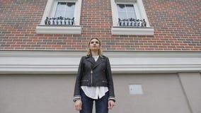 Schönes durchdachtes blondes Mädchen, das auf der Hintergrundwand eines Backsteinhauses steht Zwei Fenster stock video footage
