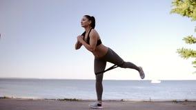 Schönes Eignungsmädchen, das Übungen auf einer Küste tut In voller Länge von einer Profisportfrau, die ihre Beine ausdehnt stock video footage