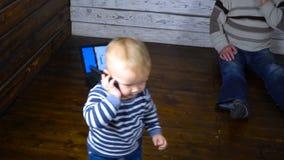Schönes einjähriges Kind wird mit einem Telefon gespielt Die goldene Taste oder Erreichen für den Himmel zum Eigenheimbesitze stock footage