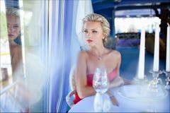 Schönes elegantes vorzügliches blondes Mädchen im roten Kleid, das an sitzt Stockfoto