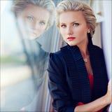 Schönes elegantes vorzügliches blondes Mädchen schaut gerade und stric Lizenzfreies Stockfoto