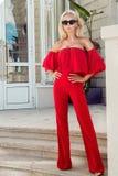 Schönes elegantes weibliches Mode-Modell im roten Kleid, das vor den Luxushotels und den Butiken steht Stockbild
