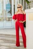 Schönes elegantes weibliches Mode-Modell im roten Kleid, das vor den Luxushotels und den Butiken steht Stockbilder