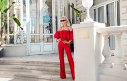 Schönes elegantes weibliches Mode-Modell im roten Kleid, das vor den Luxushotels und den Butiken steht Stockfotos