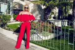 Schönes elegantes weibliches Mode-Modell im roten Kleid, das vor den Luxushotels und den Butiken steht Lizenzfreies Stockbild