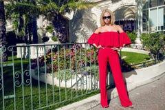 Schönes elegantes weibliches Mode-Modell im roten Kleid, das vor den Luxushotels und den Butiken steht Stockfoto