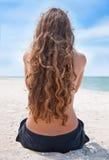 Schönes entspannendes nahes der jungen Frau das Meer lizenzfreie stockbilder