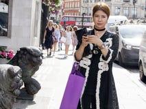 Schönes ernstes asiatisches Mädchen im schwarzen Kleid kreuzt die Straße nahe Liverpool-Straße lizenzfreies stockbild