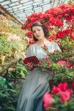 Schönes erwachsenes Mädchen in einem Azaleengewächshaus ein Buch lesend und in einem schönen Retro- Kleid träumend stockfoto