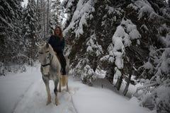 Schönes europäisches Mädchenreiten auf einem beige Pferd in der Winterwaldfrau, die ein Pferd umarmt stockfoto