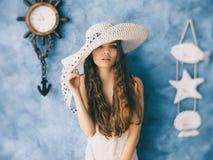 Schönes feenhaftes Mädchen im Hut, der auf blauem Hintergrund steht Stockfotografie