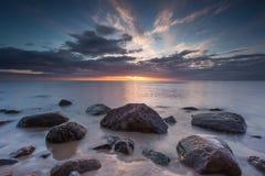 Schönes felsiges Seeufer bei Sonnenaufgang oder Sonnenuntergang Stockfotografie