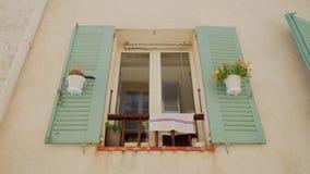 Schönes Fenster mit offenen, grünen Fensterläden und Blumen in hängenden Blumentöpfen auf beige Wand des mediterranen Hauses stock video