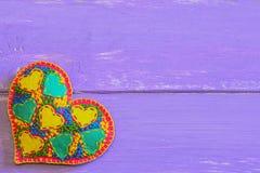 Schönes Filzherz für Valentinsgruß-Tag Gesticktes Herz vorhanden auf purpurrotem hölzernem Hintergrund mit leerem Platz für Text Stockbild