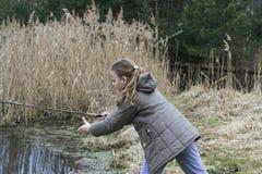 Schönes Fischen des kleinen Mädchens mit dem Spinnen auf den Fluss Lizenzfreies Stockbild