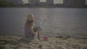 Schönes Fischen des kleinen Mädchens mit spinnender Stange stock video