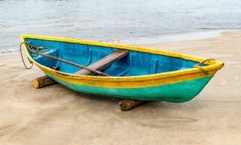 Schönes Foto des auf den Strand gesetzten Fischereikanus, das Kanu wird bunt in der traditionellen asiatischen Art gemalt Es ist  lizenzfreies stockbild