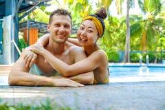 Schönes Foto des glücklichen Paars im Pool plaudernd mit einander stockbilder