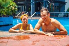 Schönes Foto des glücklichen Paars im Pool plaudernd mit einander stockfoto