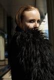 Schönes Frauenbaumuster in der warmen Jacke des Modeschwarzen mit flaumigem Pelz Stockfoto