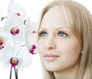 Nahaufnahmefrauengesicht mit weißer Orchidee Stockbild